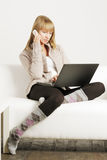 Blonde on sofa with laptop and cellphone Royalty Free Stock Photos