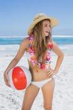 Blonde sonriente apto en el sombrero blanco del bikini y de paja que sostiene la pelota de playa Fotografía de archivo