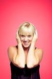 Blonde sonriente con el auricular que escucha la música Fotografía de archivo libre de regalías