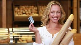 Blonde sonriente con las bolsas de papel que muestran la tarjeta de crédito almacen de metraje de vídeo