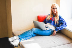 Blonde sonriente con un ordenador portátil en una oficina moderna Foto de archivo libre de regalías