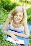 Blonde sorridente con un libro Fotografie Stock