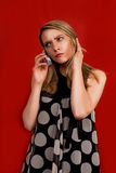 Blonde speaking on phone. Standing turned right with hands lifted up stock photo