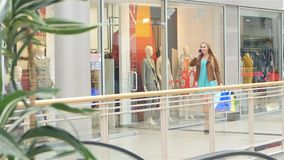 Blonde speaks on a mobile phone and walks around. Blonde with shopping bags around  walks around the glass shop windows, Slow motion stock video footage