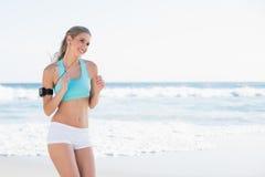 Blonde sportive de sourire dans le fonctionnement de vêtements de sport photo libre de droits