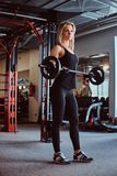 Blonde sportive female in sportswear doing exercise on biceps with a barbell in a fitness club or gym. Blonde sportive female in sportswear doing exercise on royalty free stock images