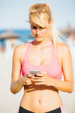 Blonde Sportlerin, die Mobile auf Strand verwendet Stockbilder