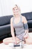 Blonde sportliche Dame überprüft im Blutdruck. Stockbild
