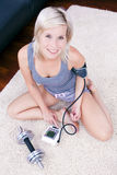 Blonde sportliche Dame überprüft im Blutdruck. Stockfotografie