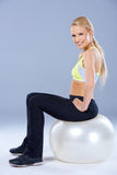 Blonde sportliche Frau, die auf Eignungsball sitzt Stockfotografie
