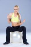 Blonde sportliche Frau, die auf Eignungsball sitzt Stockfotos