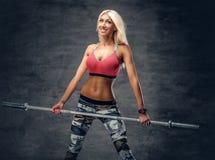 Blonde sportliche Frau hält Barbell Stockfotos