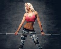 Blonde sportliche Frau hält Barbell Stockfoto
