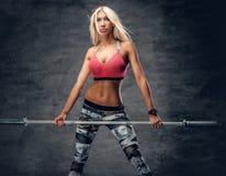 Blonde sportliche Frau hält Barbell Stockfotografie