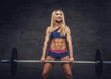 Blonde sportliche Frau mit Barbell Stockfotos