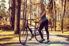 Blonde sportliche weibliche Aufstellung mit Fahrrad Stockbilder