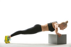 Blonde sports girl with cube stand Royalty Free Stock Images