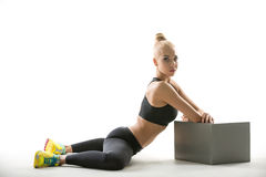 Blonde sports girl with cube stand Stock Photos