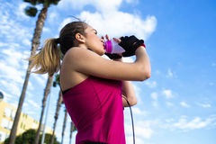 Blonde sportswoman while drinking water after running Stock Photography