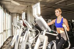 Blonde sporty woman in fitness club or gym, ride on orbitrack stock photos