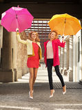 Blonde springende Frauen mit bunten Regenschirmen Lizenzfreies Stockfoto