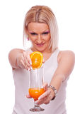 Blonde squeezing orange Stock Images