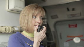 Blonde srewardess give instructions to passengers at the airplane stock footage