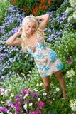 Blonde Stütze der Schönheit nahe Blumenrasen Stockfoto