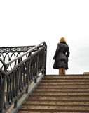 Blonde, Stairs and railings, metal construction. Blond, stone steps, iron castings, the woman standing at the top, place for a slogan, lettering or logo Stock Image