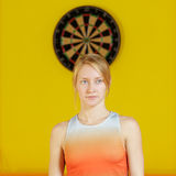 Blonde standing against darts ring Royalty Free Stock Photos