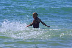 Blonde standing in surf Stock Image