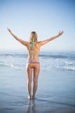 Blonde Stellung auf dem Strand im Bikini mit den Armen heraus Lizenzfreie Stockfotografie