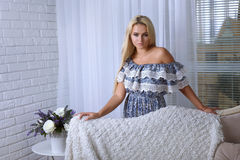 Blonde Stellung hinter dem Sofa Stockbild