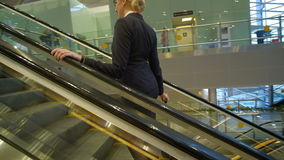 Blonde stewardess rides up on escalator with suitcase at airport. Young air hostess waits before flight goes upstairs, smiles, looks at camera. Fair-haired stock video footage
