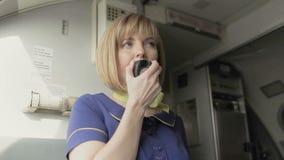 Blonde stewardess speaks to the loadspeaker in the cabin of airplane stock footage