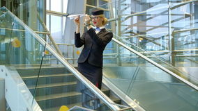 Blonde stewardess standing on stairs making toy paper plane in hall. Young airhostess waits before flight entertaining makes planes, runs up in air at airport stock footage