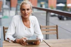 Blonde stilvolle Frau in der eleganten schwarzen Kleidung sprechend am Telefon Stockfotos