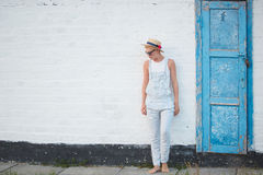 Blonde stilvolle Frau der recht dünnen Sonnenbräune bei der Strohhut- und Sonnenbrilleaufstellung Lizenzfreie Stockfotos