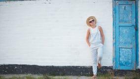 Blonde stilvolle Frau der recht dünnen Sonnenbräune bei der Strohhut- und Sonnenbrilleaufstellung Stockbild
