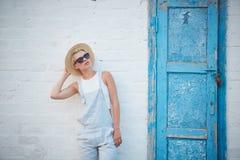 Blonde stilvolle Frau der recht dünnen Sonnenbräune bei der Strohhut- und Sonnenbrilleaufstellung Stockfoto