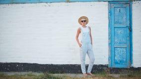 Blonde stilvolle Frau der recht dünnen Sonnenbräune bei der Strohhut- und Sonnenbrilleaufstellung Lizenzfreie Stockbilder