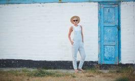 Blonde stilvolle Frau der recht dünnen Sonnenbräune bei der Strohhut- und Sonnenbrilleaufstellung Lizenzfreies Stockfoto