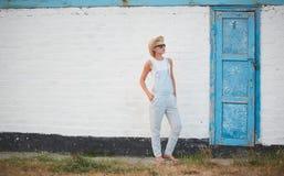 Blonde stilvolle Frau der recht dünnen Sonnenbräune bei der Strohhut- und Sonnenbrilleaufstellung Stockbilder