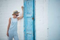 Blonde stilvolle Frau der recht dünnen Sonnenbräune bei der Strohhut- und Sonnenbrilleaufstellung Stockfotografie