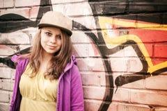 Blonde stilvolle Jugendliche steht nahe städtischem wal Lizenzfreie Stockfotos