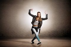 Blonde street girl crossed her legs and depicting gesture. Complex of movements stock image