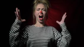 The clown clown with a red nose screams and waves her hands stock footage