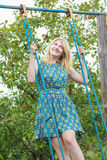 Blonde student girl in azure blue silk sundress standing on handmade swing Stock Photos