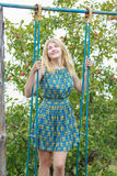 Blonde student girl feminine silk sundress is standing on handmade swing Royalty Free Stock Photography