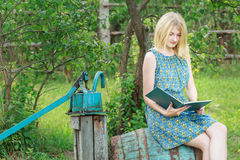 Blonde student girl in garden is reading book with blue cover Royalty Free Stock Images